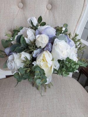Vakker håndlaget brudebukett i hvitt, kremhvit og lavendel. Laget med kunstige roser, hortensia, pioner og grønn eukalyptus. Stilkene på brudebuketten er dekorert med kremhvite silkebånd.